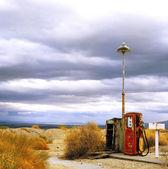 Fotografie staré benzinové pumpy na okraji pouště