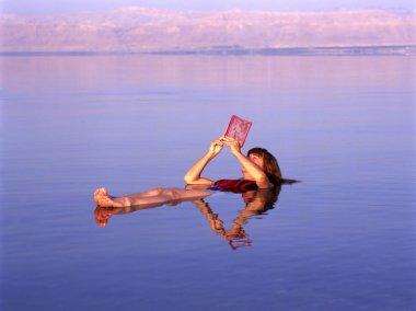 Girl reading a book in the Dead Sea