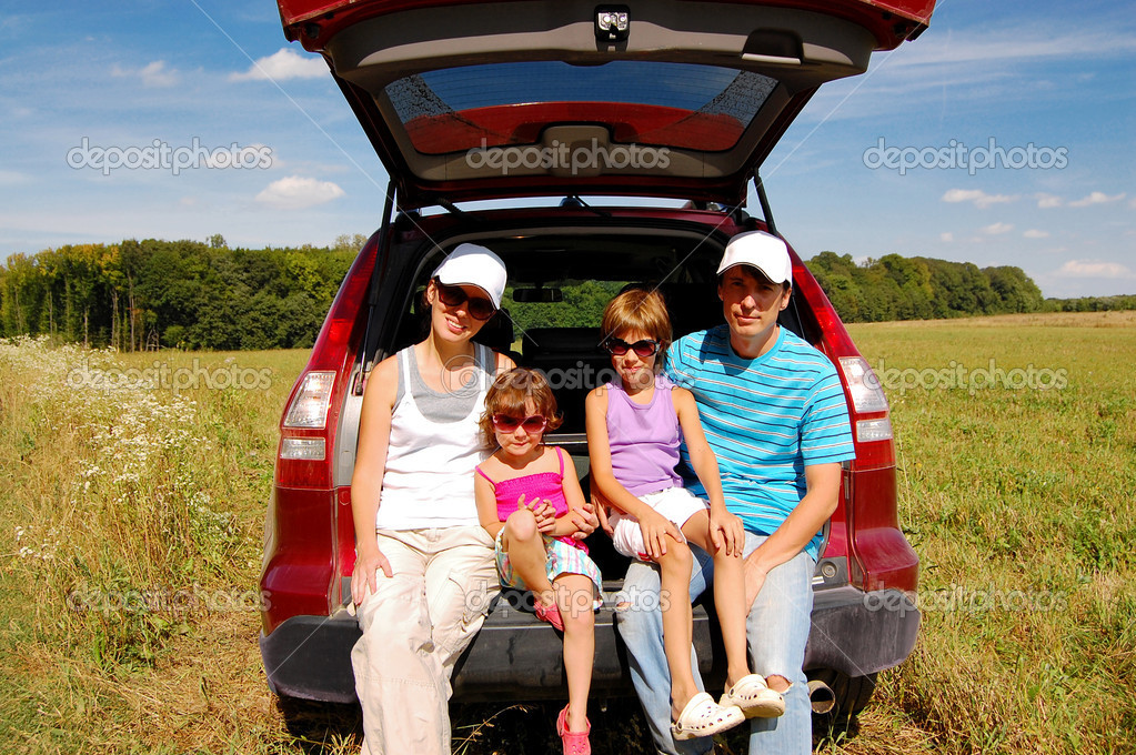 Happy smiling family of four near their car on vacation trip