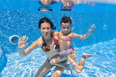 Active underwater smiling family in swimming pool