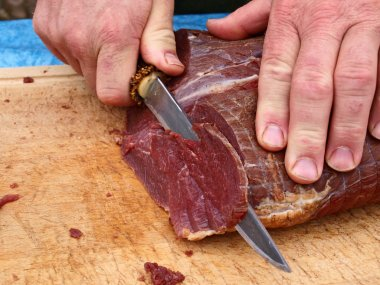 Cut smoked roasted meat beef by a chef