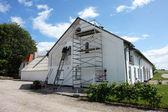 Fotografia uomo su ponteggi dipinto una casa