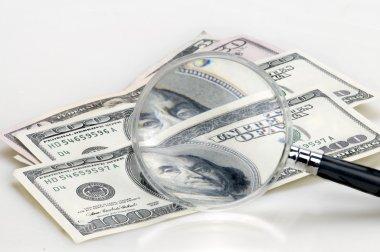 Dollar bills on the magnifying glass