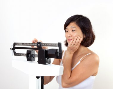 Woman Weighing Herself on Weight Scale