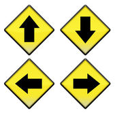 skupina čtyř žluté dopravní značky s šipkami