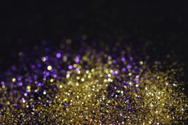 Gold and purple glitter on black background