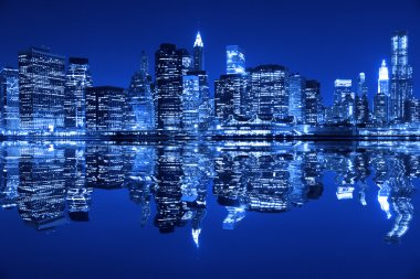 Lower Manhattan in New York City at night with reflection in water with blue hue stock vector