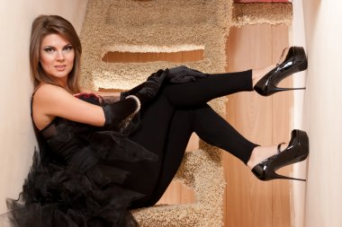 Beautiful young woman in high heels shoes sitting on stairs