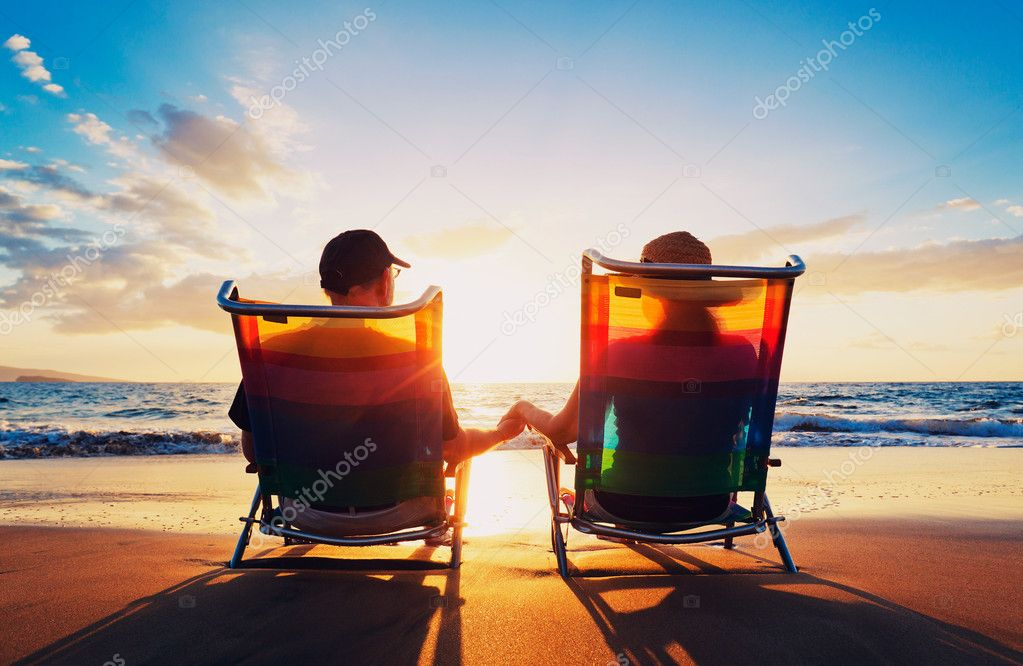 Senior couple of old man and woman sitting on the beach watching