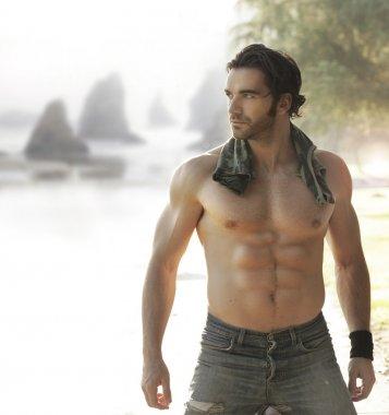 Hunk with muscular body near a beach