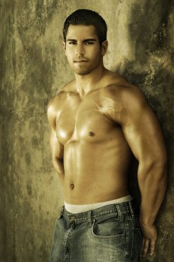 Young bodybuilder against wall