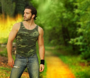 Portrait of a muscular young man in beautiful natural setting we