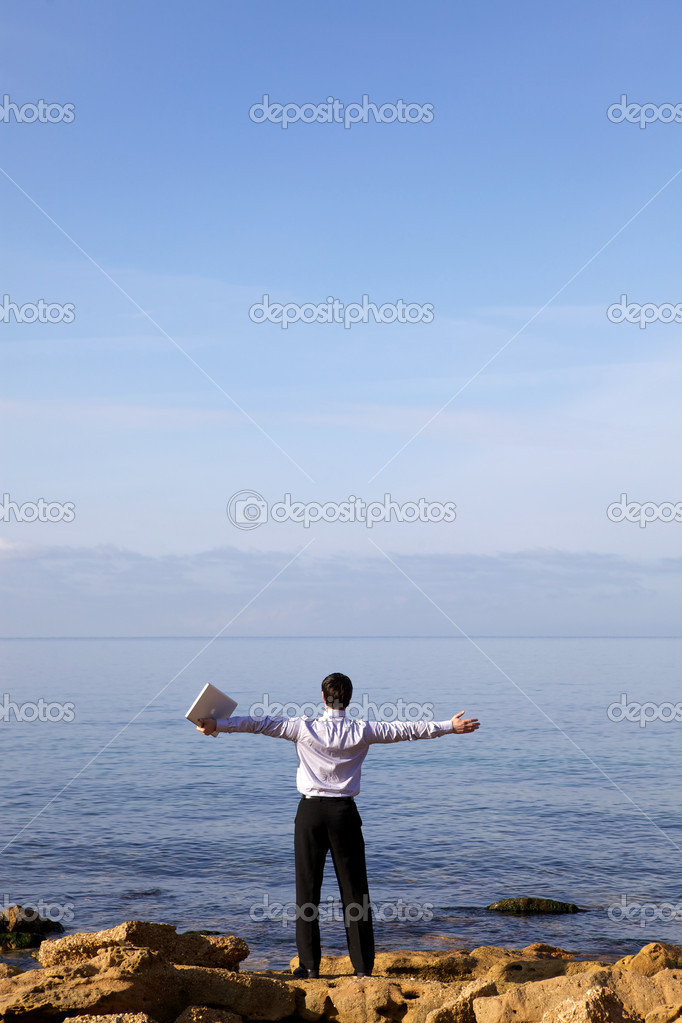 Man near sea with laptop