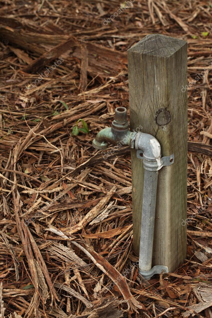 A Short Metal Tap Water Next to a Wooden Pole at the Park