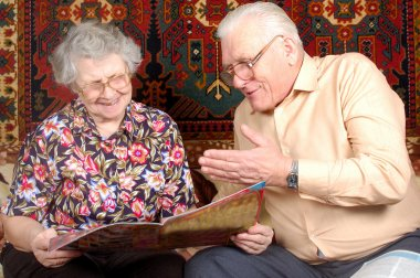 Senior couple read the news and smile