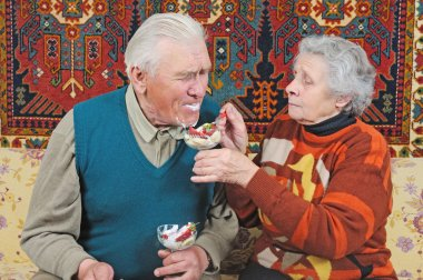 Old woman feed old man