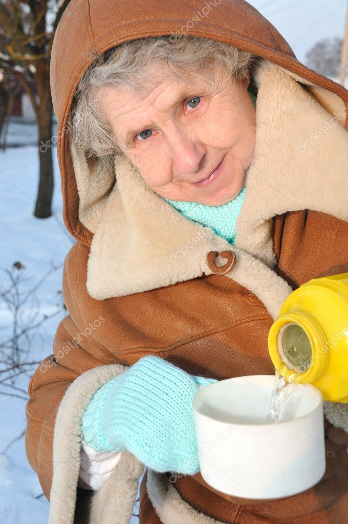 Happy granny with thermos on winter background