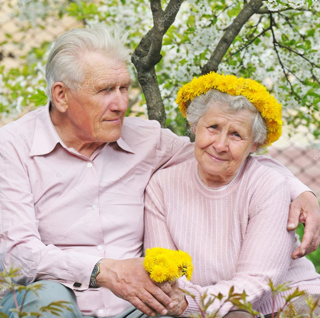 Old couple against a background of flowering garden