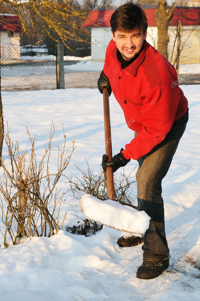 Adult man clean owns yard against snow