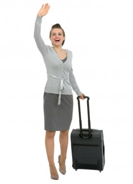 Excited traveling woman with suitcase waving hand