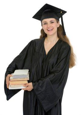 Graduation female student holding stack of books