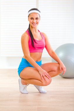 Smiling fit young girl squatting down