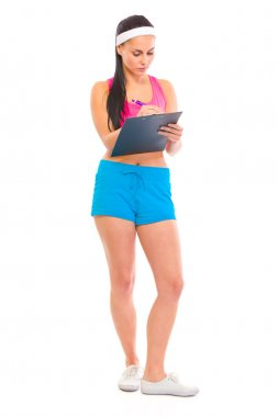 Serious young fitness trainer making notes in training plan