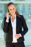 Usmívající se obchodní žena mluví na mobil na kancelářská budova