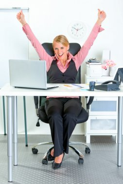 Excited business woman sitting at office desk and rejoicing her success