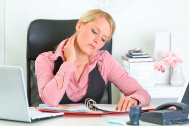 Tired business woman sitting at office desk and working