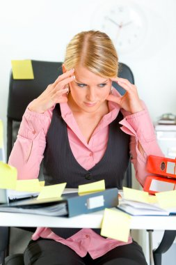 Tired business woman sitting at workplace overwhelmed with sticky reminder