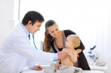 Surprised baby being checked by a doctor using a stethoscope