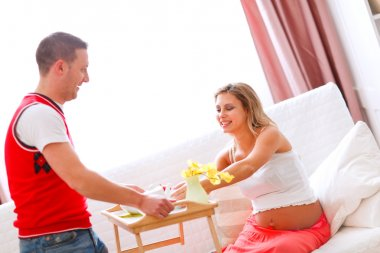 Young man bring breakfast to his happy pregnant wife