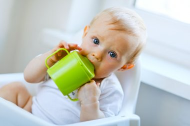 Lovely baby girl sitting in chair and drinking from baby cup