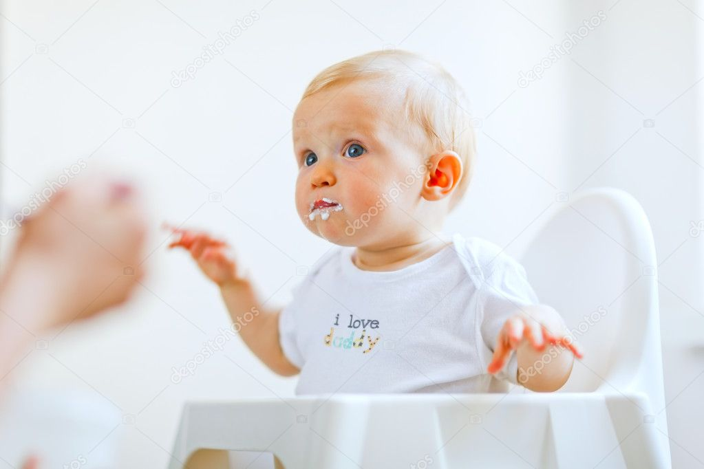 eat smeared lovely baby in baby chair feeding by mother — stock