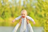 Fotografie Mutters Hände halten lachend Ausdruck Baby gegen sonnigen Blätter