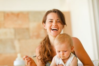 Portrait of laughing young mother feeding baby