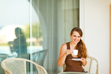 Smiling young woman sitting on terrace and drinking coffee