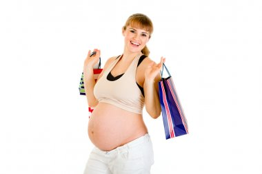 Beautiful pregnant woman holding shopping bags in hands