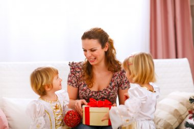 Happy mother holding gift of her twins daughters