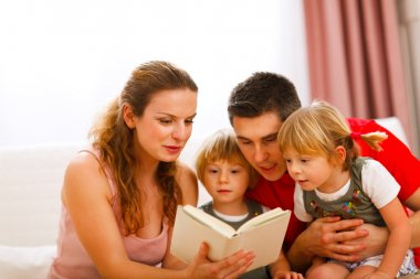 Parents reading to twins daughters