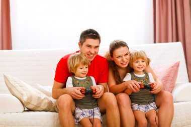 Mother and father playing with twins daughter on console