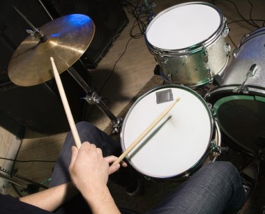Drummer playing drumset.