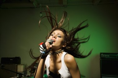 Female singing into mic.