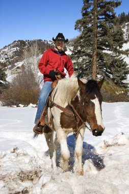 Man horseback riding in snow.