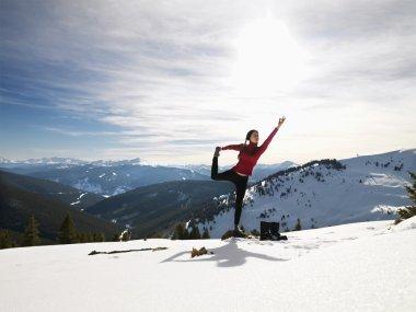Woman doing yoga in snow.