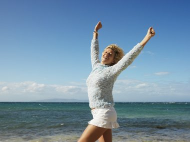 Portrait of attractive young blond woman smiling with arms raised in air on Maui, Hawaii beach. stock vector