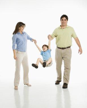 Parents swinging son.