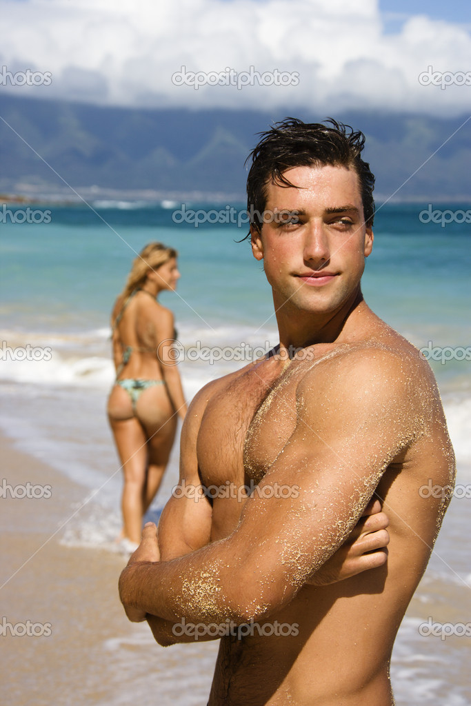 Man posing on beach.