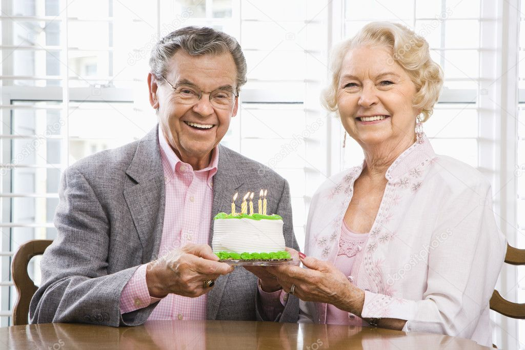 Mature Caucasian couple holding birthday cake looking at viewer.